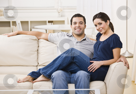 Couple on Couch stock photo, An attractive young couple lounging on a couch together.  The female is sitting on the male's lap.  They are facing the camera and are smiling. Horizontally framed photo. by Jonathan Ross