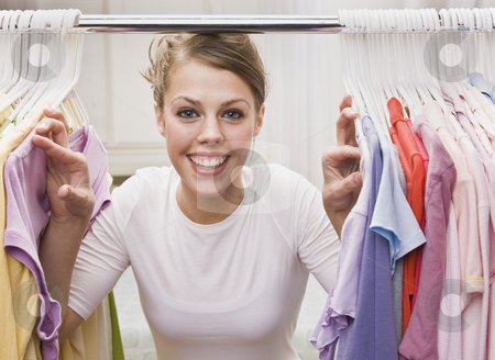 Woman looking through closet stock photo, A young, attractive woman is standing in a closet and looking through clothes.  She is smiling at the camera.  Horizontally framed shot. by Jonathan Ross