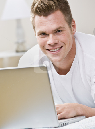 Attractive Man with Laptop stock photo, An attractive young man smiling and using a laptop.  Vertically framed shot. by Jonathan Ross