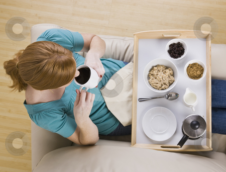 Top View of a Woman and Breakfast Tray stock photo, A woman sitting with a breakfast tray on her lap.  She is drinking coffee. Horizontally framed shot. by Jonathan Ross