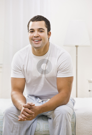 Man Sitting On Bed and Smiling stock photo, A man sitting on the edge of a bed and smiling. He is facing the camera. Vertically framed photo. by Jonathan Ross