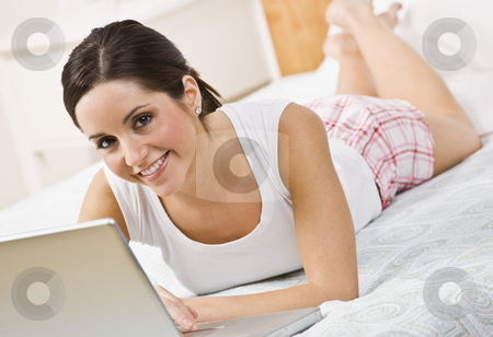 Beautiful Brunette Using Laptop stock photo, A beautiful brunette relaxing on her bed and using a laptop.  She is smiling directly at the camera.  Horizontally framed shot. by Jonathan Ross