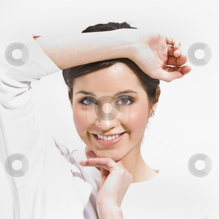 Female Posing stock photo, An attractive female posing.  She is framing her face with her hands and is smiling directly at the camera.  Square framed shot. by Jonathan Ross