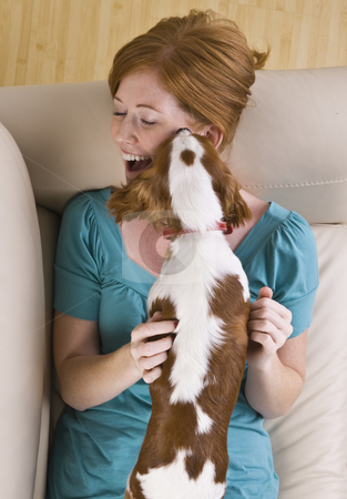 Dog Licking Woman stock photo, A young woman lying on a couch and being licked by a dog that she is holding.  She is smiling and has her eyes closed. Vertically framed shot. by Jonathan Ross