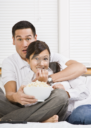 Scared Couple Watching TV stock photo, A young, attractive couple is sitting together in bed and watching TV.  They look shocked or scared, and are looking at the camera. Horizontally framed shot. by Jonathan Ross