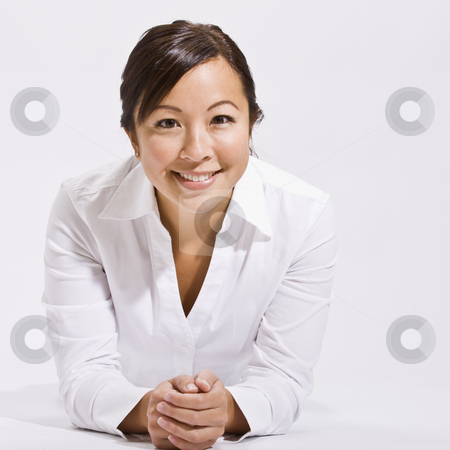 Woman Smiling at Camera stock photo, A young woman wearing white is in an isolated white room and is smiling at the camera.  Square framed shot. by Jonathan Ross