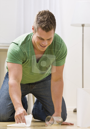 Man Cleaning Spill stock photo, An attractive young man cleaning up a spilled drink.  He is smiling. Vertically framed photo. by Jonathan Ross