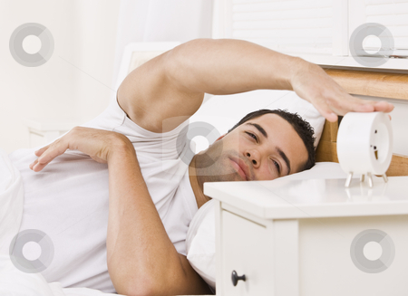 Man with Alarm Clock stock photo, A man lying in bed.  He is reaching his arm to touch an alarm clock.  He looks tired. Horizontally framed shot. by Jonathan Ross