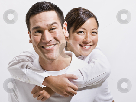 Attractive Young Couple Posing stock photo, An attractive young couple posing together.  They are smiling directly at the camera.  Horizontally framed shot. by Jonathan Ross