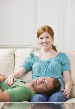Couple Relaxing on Couch Together. stock photo, Attractive man lying down on a couch with his head in a woman's lap. Vertically framed photo. by Jonathan Ross