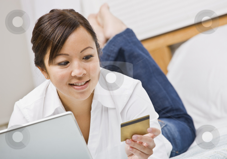 Woman with Credit Card stock photo, An attractive young woman lying on a bed and gazing at a credit card.  She is holding a laptop and is smiling. Horizontally framed photo. by Jonathan Ross