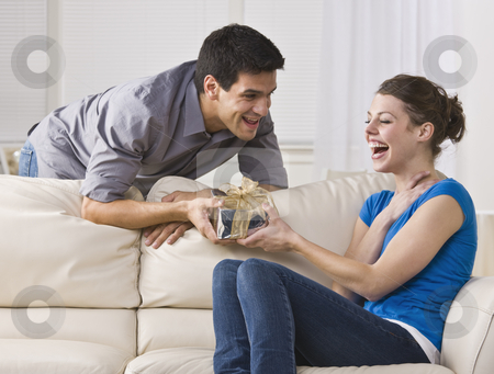 Woman laughing at gift stock photo, Man giving laughing woman gift. horizontal by Jonathan Ross