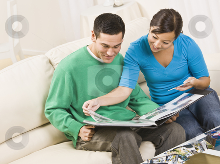 Happy Couple Viewing Photo Album stock photo, An attractive and happy asian couple sitting together on a couch and viewing a photo album together.  They are smiling.  Horizontally framed shot. by Jonathan Ross