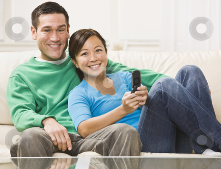 Couple Watching Television stock photo, An attractive young couple sitting on a couch and watching television.  They are smiling directly at the camera.  The female is holding a remote.  Horizontally framed photo. by Jonathan Ross