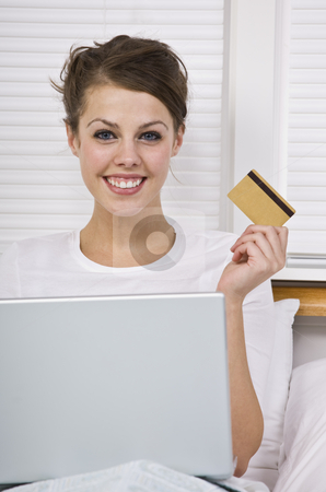 Smiling woman holding credit card stock photo, Attractive woman holding credit card with laptop and smiling at the camera. Vertically framed. by Jonathan Ross