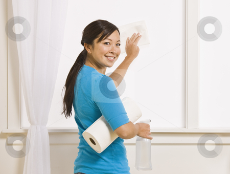 Attractive Asian Female Cleaning Window stock photo, An attractive asian young female washing a window. She is holding a roll of paper towels and has her head turned to smile toward the camera. Horizontally framed photo. by Jonathan Ross