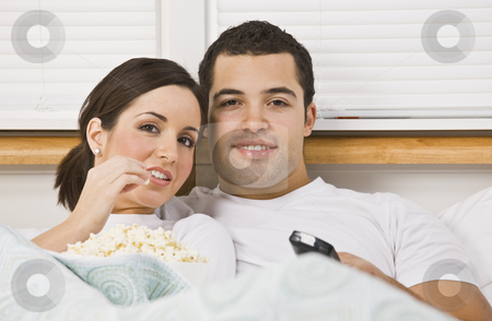 Couple Watching TV stock photo, Couple sitting in bed together. The female is eating a bowl of popcorn and the male has a television remote. Horizontally framed photo. by Jonathan Ross