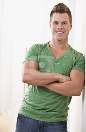 Cute man leaning on wall stock photo, Attractive man leaning on wall in green t-shirt. vertical by Jonathan Ross