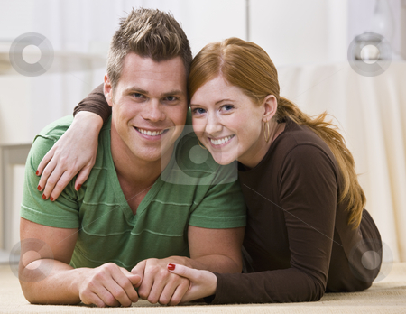 Happy Couple Lying Together On Their Apartment Floor stock photo, A young and attractive couple lying down together on their apartment floor.  They are relaxing on their stomachs and are smiling at the camera.  Horizontally framed photo. by Jonathan Ross