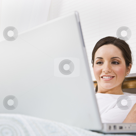 Beautiful Woman Using Laptop stock photo, A beautiful young woman is sitting in a room and working on a laptop.  She is smiling and is looking at the screen.  Square framed shot. by Jonathan Ross