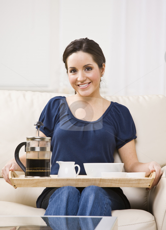 Beautiful Woman with Breakfast Tray stock photo, A beautiful young woman sitting on a couch and holding a breakfast tray.  She is smiling at the camera.  Vertically framed shot. by Jonathan Ross