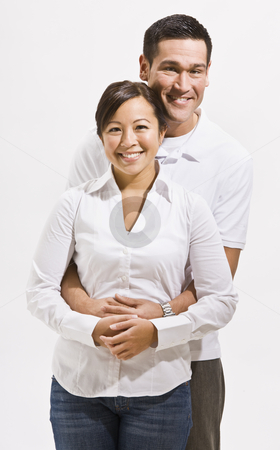 Happy Couple Posing stock photo, A happy young couple posing together.  They are smiling at the camera.  Vertically framed shot. by Jonathan Ross
