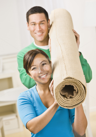 Happy Couple Carrying Carpet Roll stock photo, A happy and attractive young couple carrying a roll of carpet together.  They are smiling at the camera.  Vertically framed shot. by Jonathan Ross