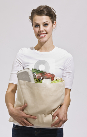 Attractive Brunette Holding Grocery Bag stock photo, Attractive woman with grocery bag in arms. vertical by Jonathan Ross