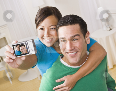 Couple Taking a Self Portrait stock photo, An attractive young couple taking their own picture with a digital camera. They are smiling.  The female is holding the camera. Horizontally framed shot. by Jonathan Ross