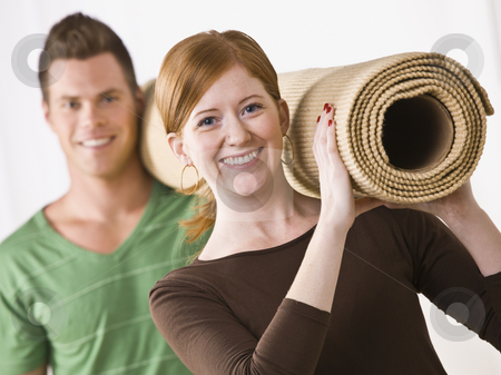 Couple Carrying Carpet Roll stock photo, A young, attractive couple is carrying a roll of carpet.  They are smiling at the camera.  Horizontally framed shot. by Jonathan Ross