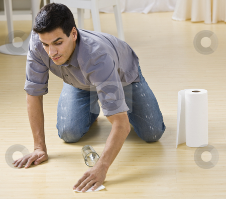 Man Cleaning Spill stock photo, A man cleaning up a spilled glass of water.  He is using paper towels on a wood floor. Horizontally framed photo. by Jonathan Ross