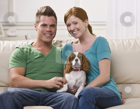 Couple Holding Dog stock photo, A young and attractive couple sitting together and holding a dog.  They are facing the camera and are smiling. Horizontally framed photo. by Jonathan Ross