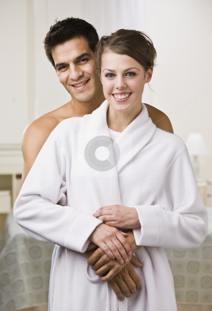 Couple Relaxing and Hugging Each Other stock photo, An attractive young couple looking relaxed and happy. The female is wearing a bathrobe and they are smiling directly at the camera. Vertically framed photo. by Jonathan Ross