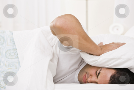 Tired Man stock photo, A tired looking man holding a pillow over his head and lying in bed.  Horizontally framed shot. by Jonathan Ross