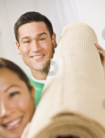 Attractive Couple with Roll of Carpet stock photo, An attractive young couple holding a roll of carpet.  They are smiling at the camera. Vertically framed photo. by Jonathan Ross