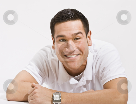 Happy Man Smiling at camera stock photo, A young man is isolated in a white room.  He is wearing a white T-shirt and is smiling at the camera.  Horizontally framed shot. by Jonathan Ross