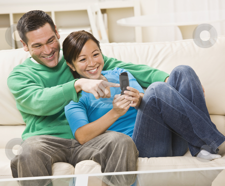 Mixed race couple watching TV together stock photo, Mixed race couple watching TV on couch with remote control. horizontal by Jonathan Ross