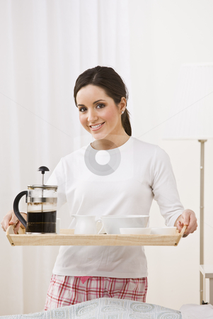 Woman Holding Breakfast Tray stock photo, A young, attractive woman is standing in her pajamas and is holding a breakfast tray.  She is smiling at the camera.  Vertically framed shot. by Jonathan Ross