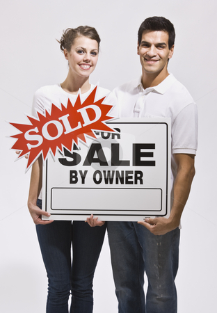 Couple Holding For Sale By Owners Sign stock photo, A young couple holding a real estate sign that reads 'sold.' They are smiling and are facing the camera. Vertically framed photo. by Jonathan Ross