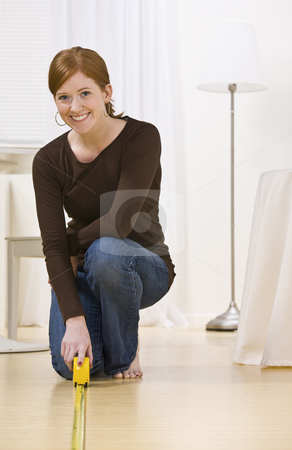 Attractive woman measuring floor stock photo, Smiling woman kneeling while measuring the floor, vertically framed by Jonathan Ross