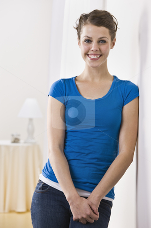 Attractive Brunette Leaning on a Wall stock photo, An attractive young female smiling directly at the camera.  Vertically framed photo. by Jonathan Ross