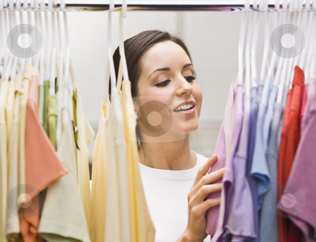Woman Going Through Her Outfits stock photo, An attractive young female looking through a clothing closet.  She is smiling.  Horizontally framed photo. by Jonathan Ross