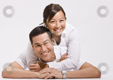 Attractive Young Couple Posing on Floor stock photo, An attractive young couple posing together on the floor.  They are smiling directly at the camera.  Horizontally framed shot. by Jonathan Ross