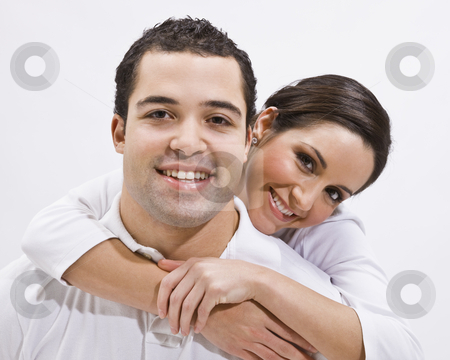 Attractive Young Couple Posing stock photo, An attractive young couple posing together.  The female has her arms around the male's neck. They are smiling directly at the camera.  Horizontally framed shot. by Jonathan Ross