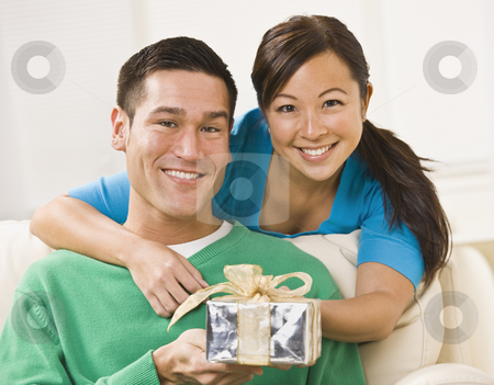 Couple Holding Present stock photo, A young couple is seated together on their couch.  They are holding a present and are smiling at the camera.  Horizontally framed shot. by Jonathan Ross