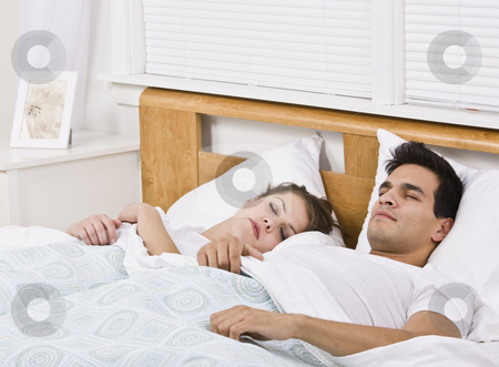 Attractive Couple Sleeping stock photo, An attractive young couple sleeping in bed together.  They look peaceful.  Horizontally framed shot. by Jonathan Ross
