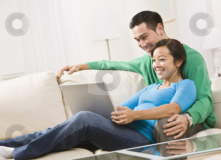 Couple Viewing Laptop stock photo, An attractive young couple on a couch, viewing a laptop screen. They are smiling. Horizontally framed shot. by Jonathan Ross