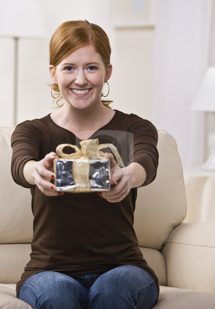 Woman Presenting Gift to the Camera stock photo, An attractive young female sitting on a couch and presenting a gift with outstretched arms.  She is looking directly at the camera and is smiling. Vertically framed photo. by Jonathan Ross