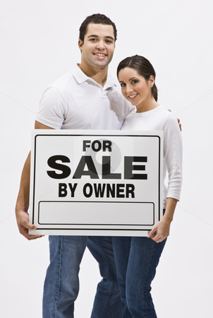 Couple With For Sale By Owner Sign stock photo, An attractive, young couple holding a 'For Sale By Owner' sign.  They are smiling and are looking directly at the camera. Vertically framed shot. by Jonathan Ross