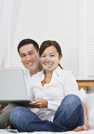 Asian couple with laptop stock photo, Attractive Asian couple sitting together with laptop. Vertically framed shot. by Jonathan Ross